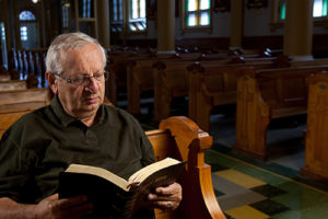 Man reading a bible in church
