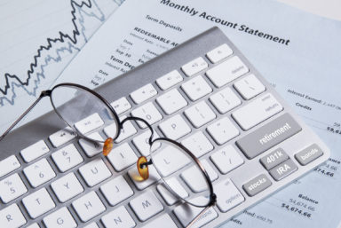 Computer keyboard on bank statement and stock chart