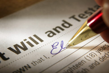 Signing Last Will and Testament. A shallow depth of field focuses putting the pen to paper finalizing the process of securing one's legacy. A red and gold ballpoint pen writes in blue ink and the writer begins to commit their name to paper in elegant blue cursive.  A pleasant reflection bounces off the gold pen.